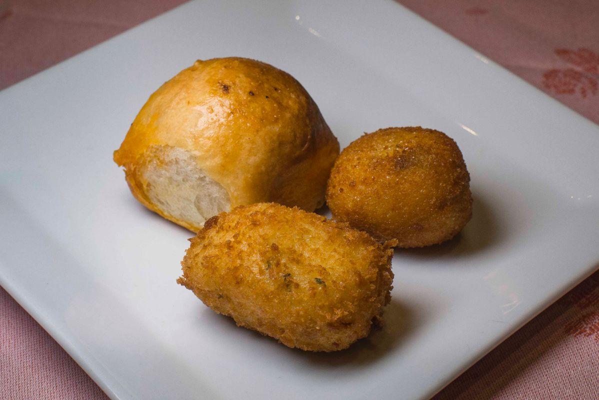 Un bollo 'preñao' y una croqueta de cocido antes del primer plato.