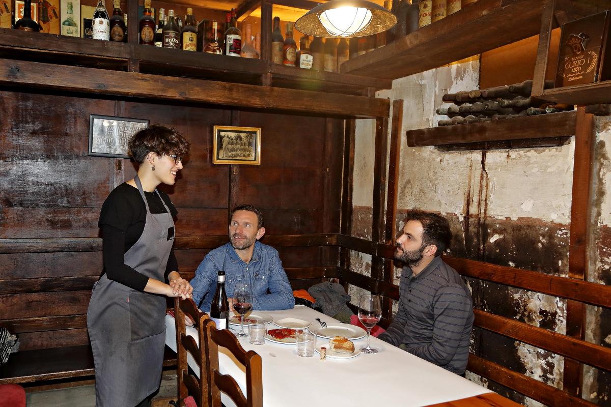 Una camarera atiende una de las mesas detrás de la que pueden verse las paredes descascarilladas por el humo.