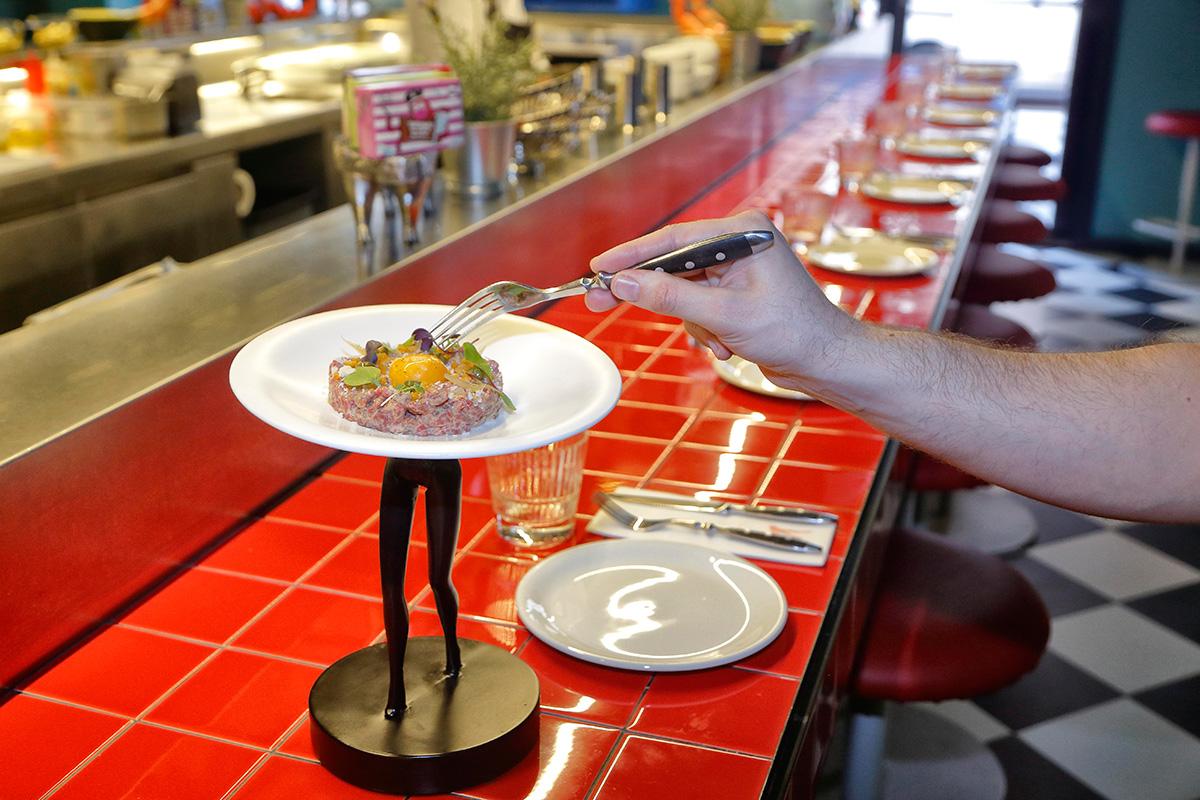 El steak tartar con patata crujiente y parmesano te lo acercan en unas piernas.