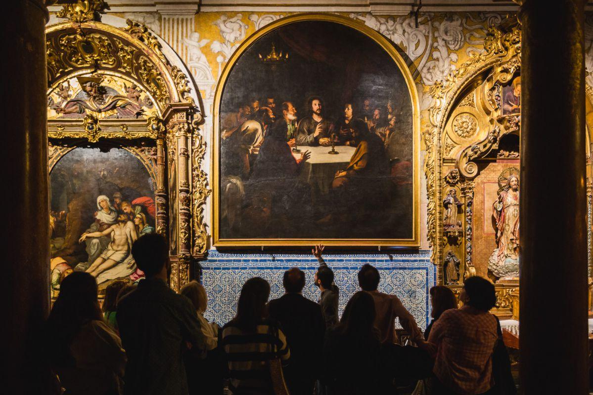 Un guía explica el cuadro de La Santa Cena de Murillo en la iglesia barroca de Santa María La Blanca durante la visita nocturna.