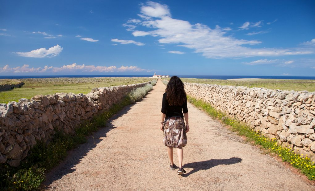 Mujer paseando por un paisaje naturista de Menorca