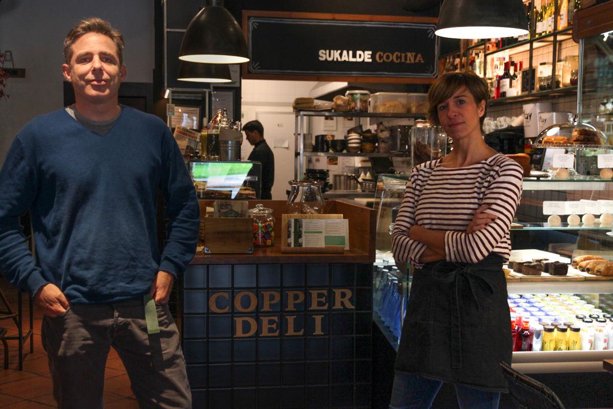Marta junto a su compañero frente al mostrador del restaurante.