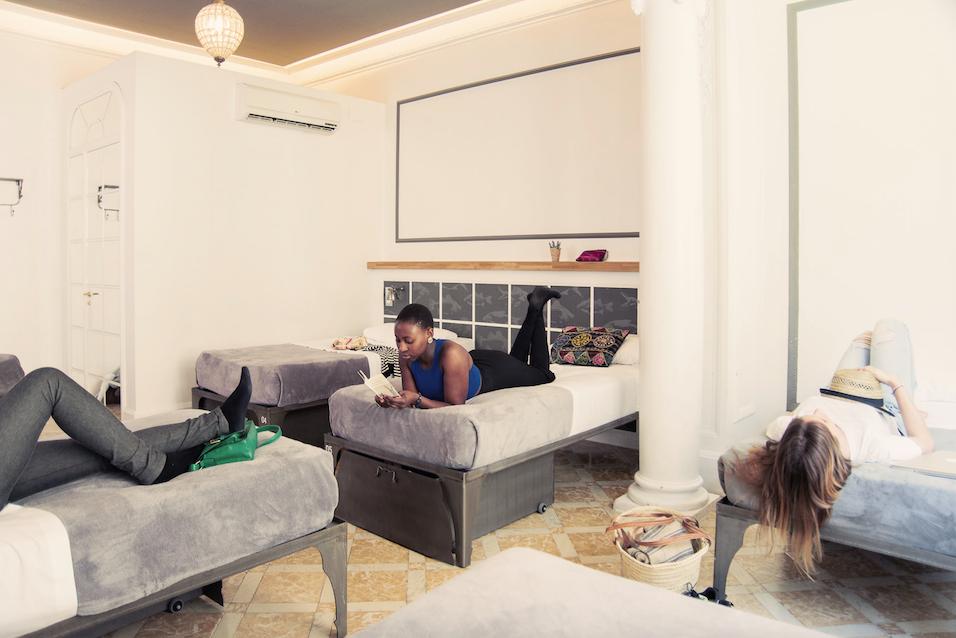 Tres personas en sus camas en una habitación con camas individuales