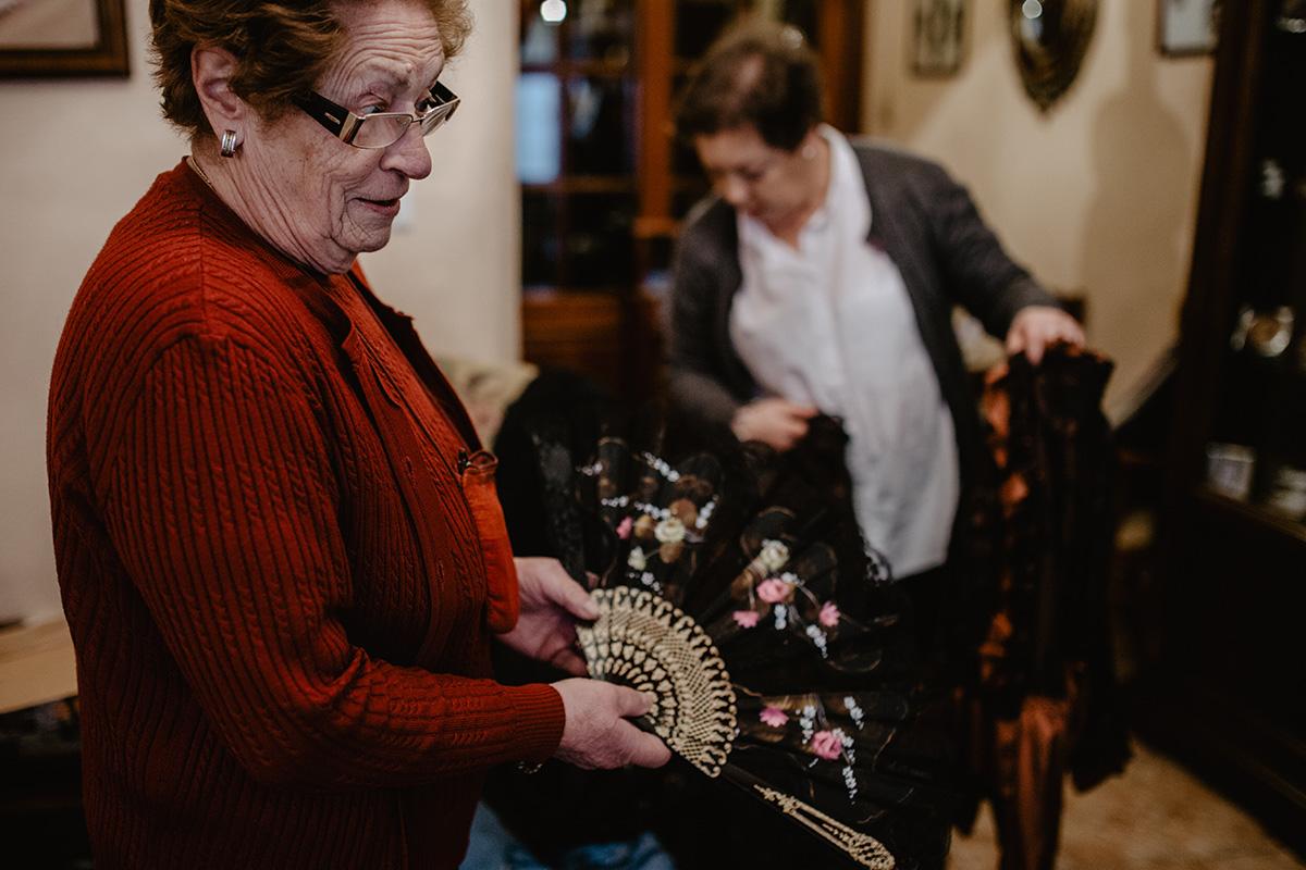 Gloria enseña un abanico de viuda mientras María busca entre los trajes de época que tienen.