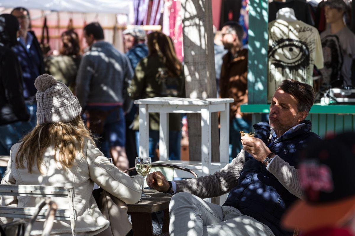 Unos extranjeros pican algo de comer y toman un vino sentados en una mesa en el mercadillo de Las Dalias, Ibiza.