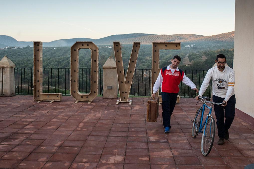 """Dos hombres: uno llevando una bicicleta y el otro una maleta en una terraza donde hay unas letras que forman la palabra """"love"""""""