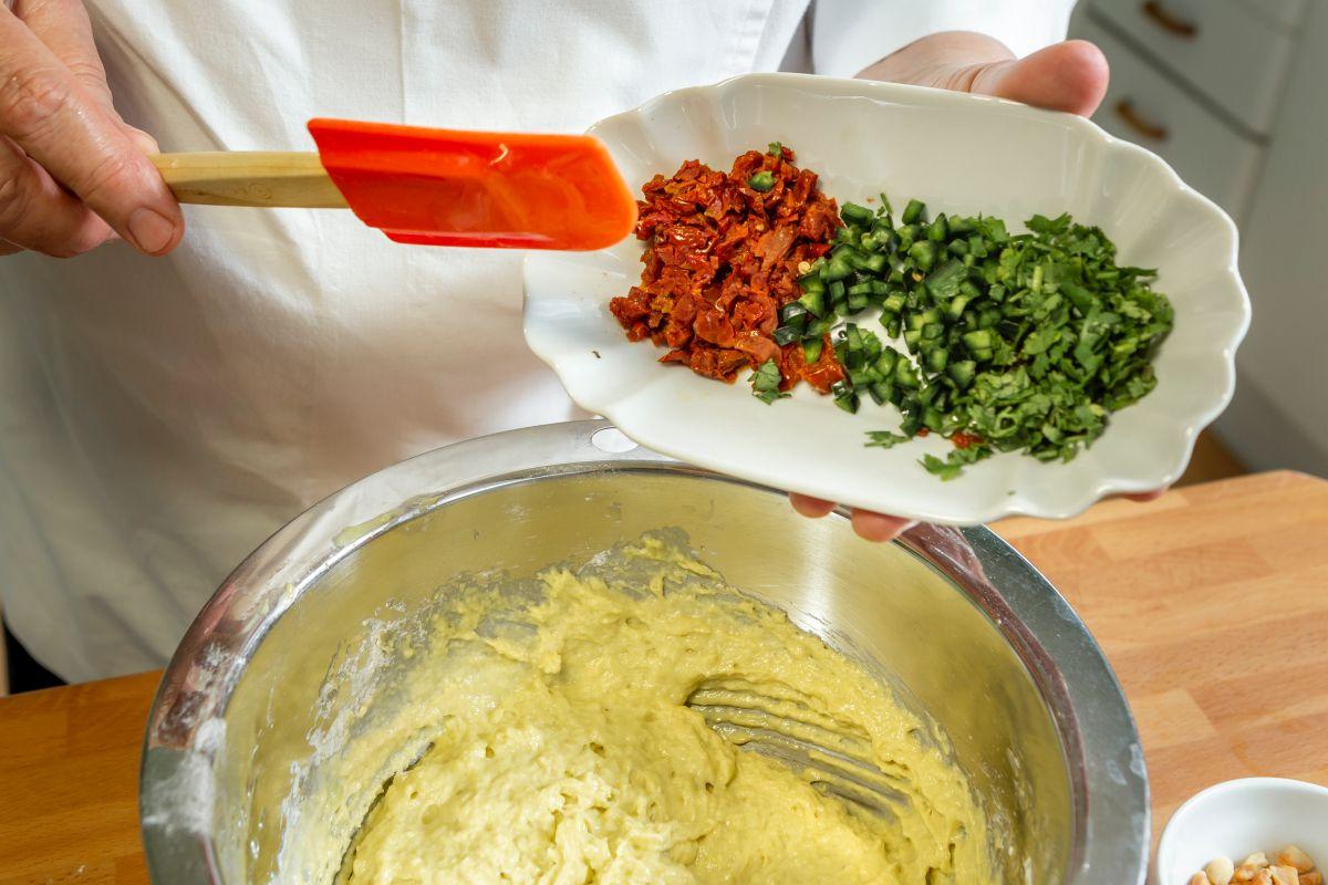 Echando los pedacitos de tomates secos y pimientos a la masa de bizcocho de aguacate.