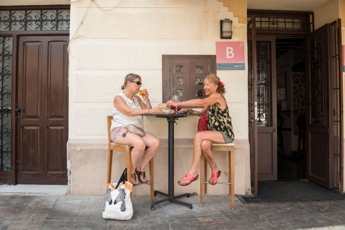 Una pareja de turistas toman unos vinos en la terraza del restaurante 'La Catedral', en Cartagena, Murcia.