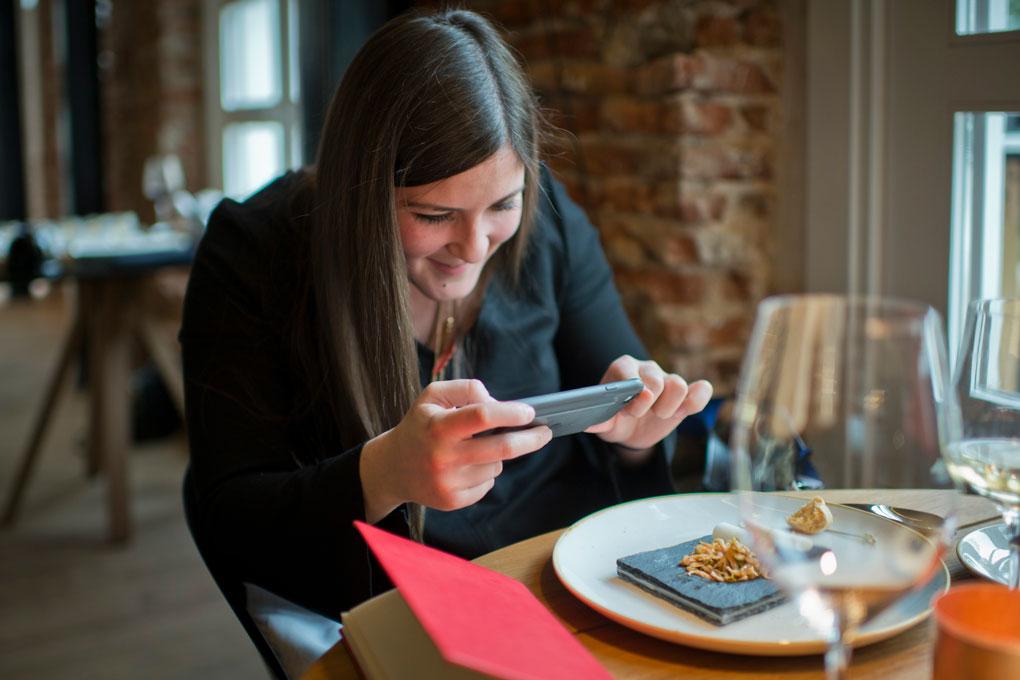 Una invitada fotografía junto a los ventanales un plato con camarones con lima.