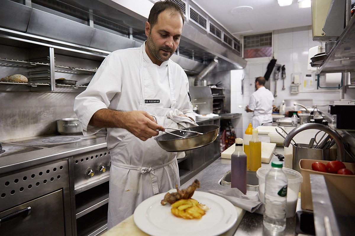 El jefe de cocina acabando un plato de cabrito al horno.