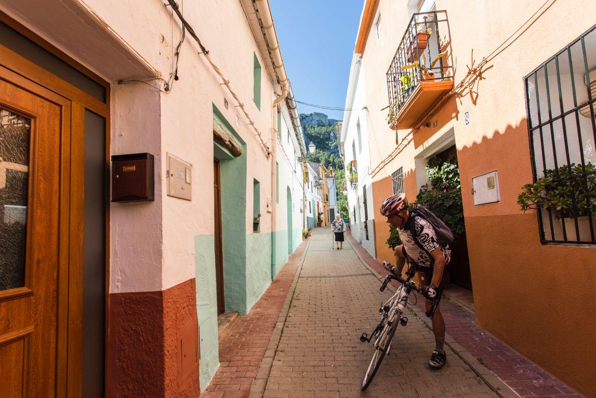 Un ciclista paseando por una calle en Benirrama, Valle de la Gallinera, Valencia.