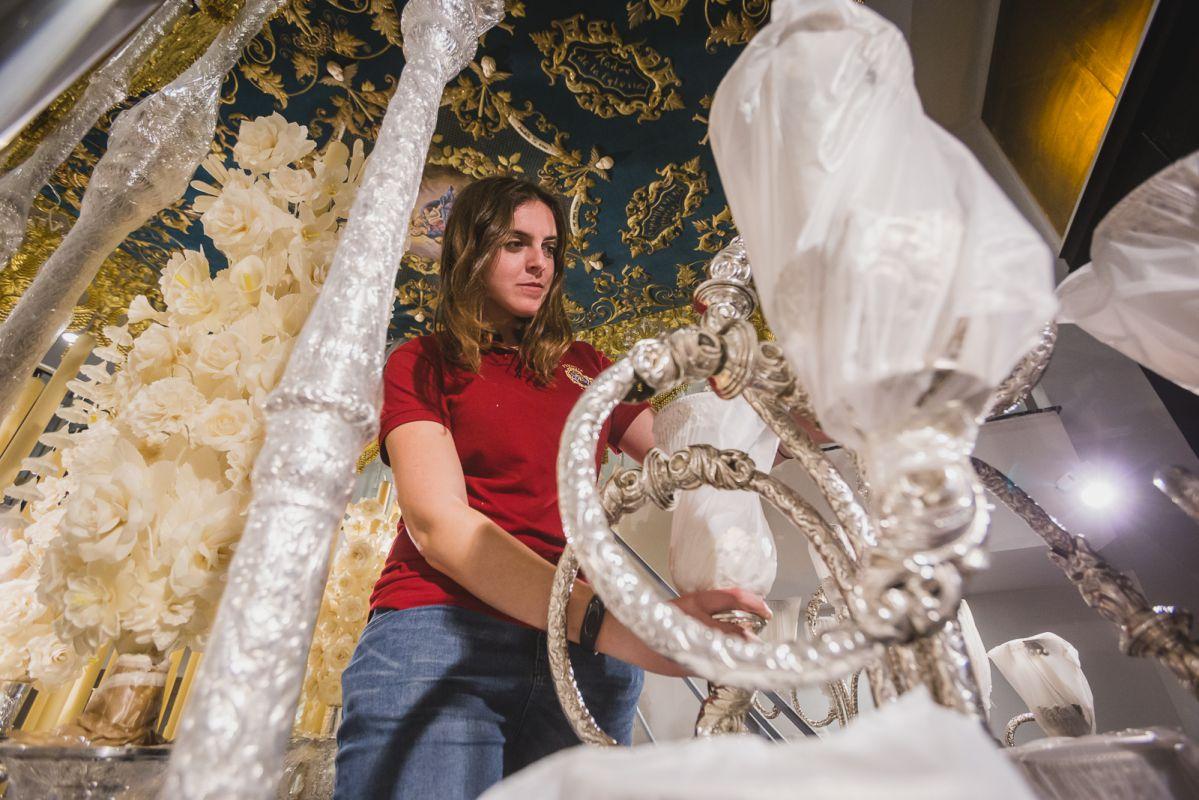La joven auxiliar de priostía coloca los guardabrisas de los candelabros de cola del palio de la Virgen de Consolación.