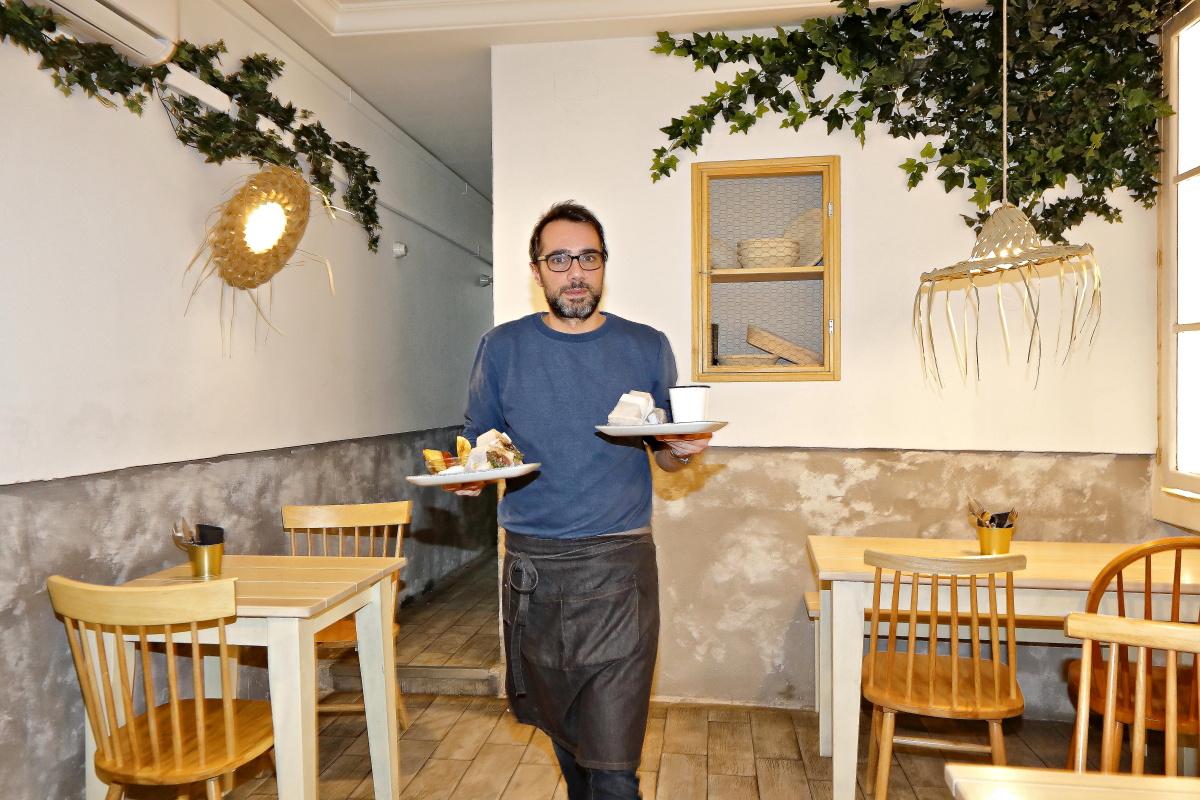 El dueño del local 'Crumb', en Madrid, recogiendo una mesa.