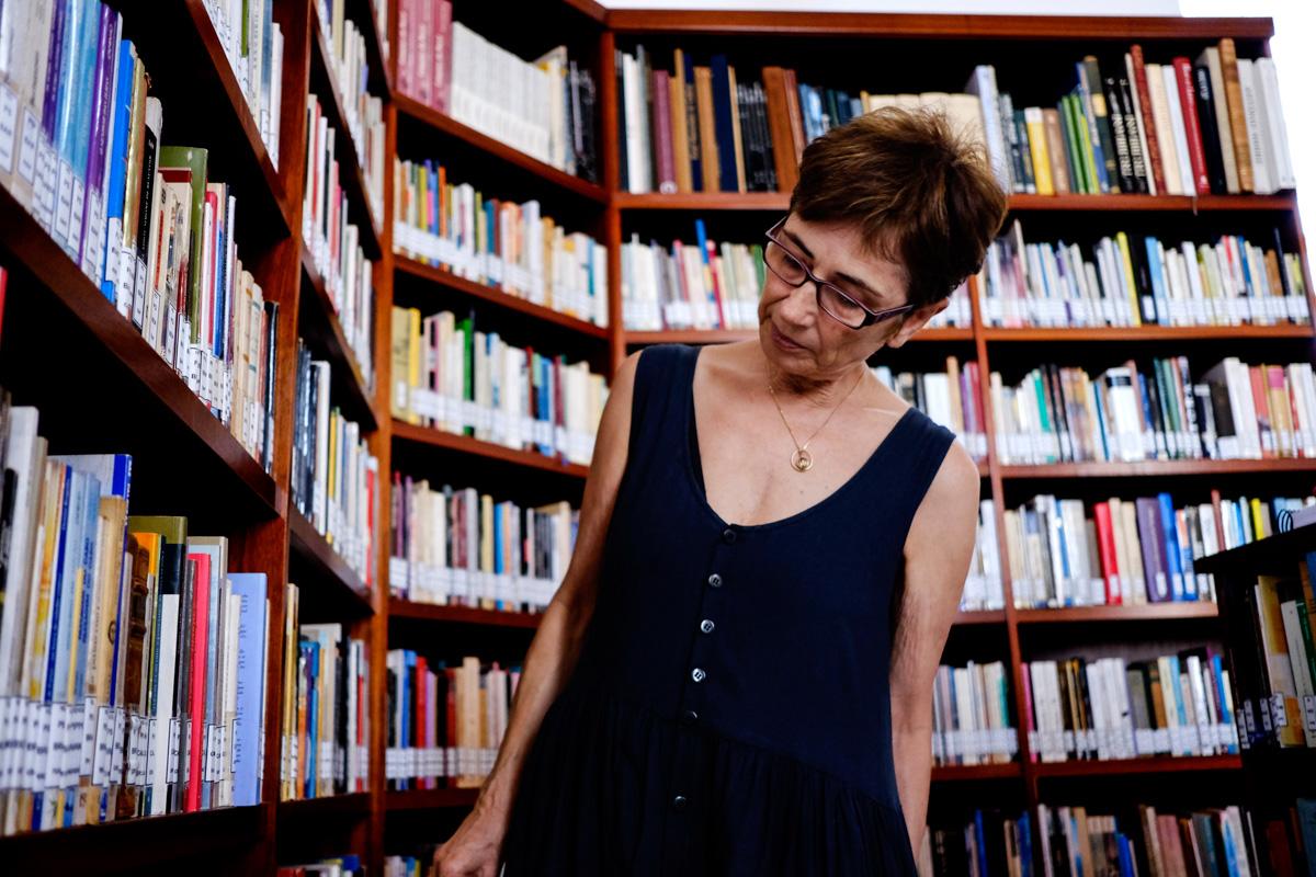 La viuda del escritor posa en la sección de la biblioteca dedicada a escritoras.