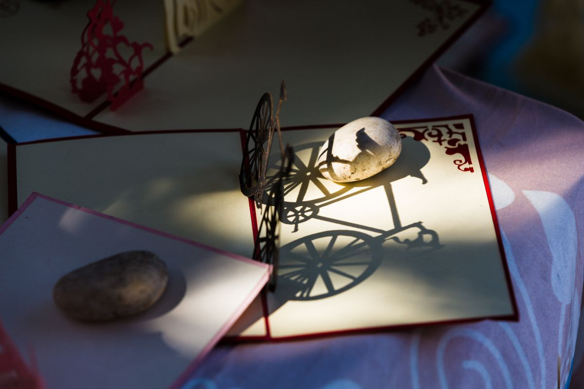 Detalle de la sombra de una bicicleta de alambre sobre un pergamino y unas piedras, en el mercadillo de Las Dalias, Ibiza.