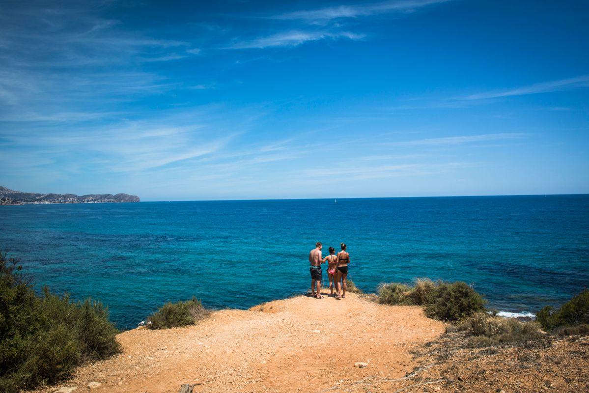 Unos bañistas miran hacia el mar en la cala del Peñón de Ifach, en Calpe, Alicante.