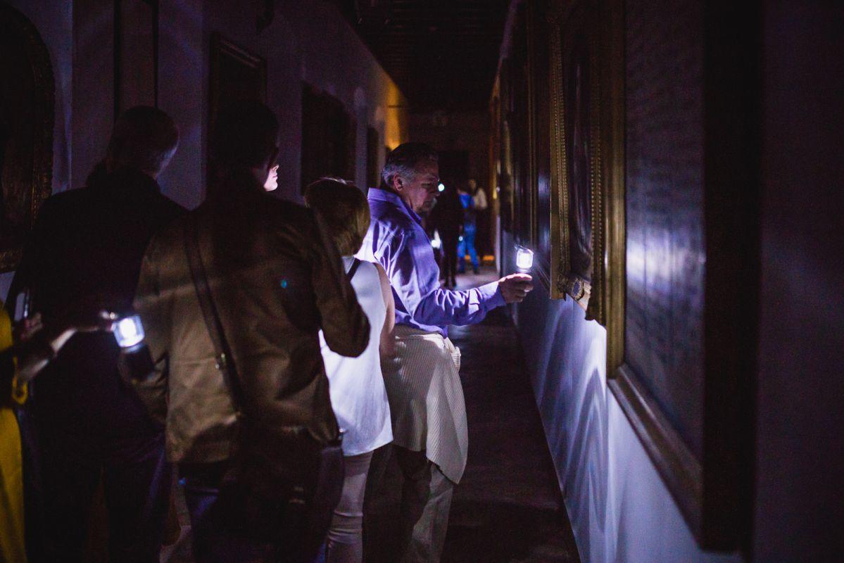 Un grupo de visitantes recorren con pequeños candiles los pasillos repletos de obras del Hospital de la Caridad, Sevilla.