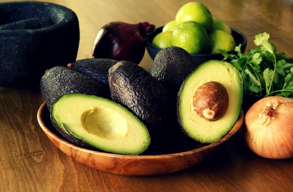 Aguacate, lima, cebolla y cilantro son los ingredientes del guacamole, que se prepara en molcajete.