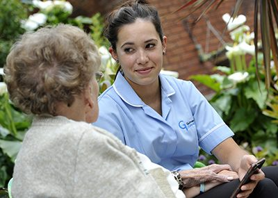 Young carer showing older woman her mobile phone.