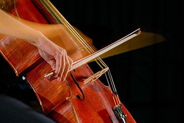 Hand mit Wischeffekt an einem Streichinstrument