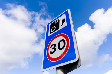 30mph speed limit sign with a speed camera warning
