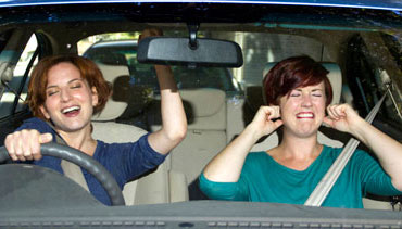 One woman singing and one woman covering her ears in a car