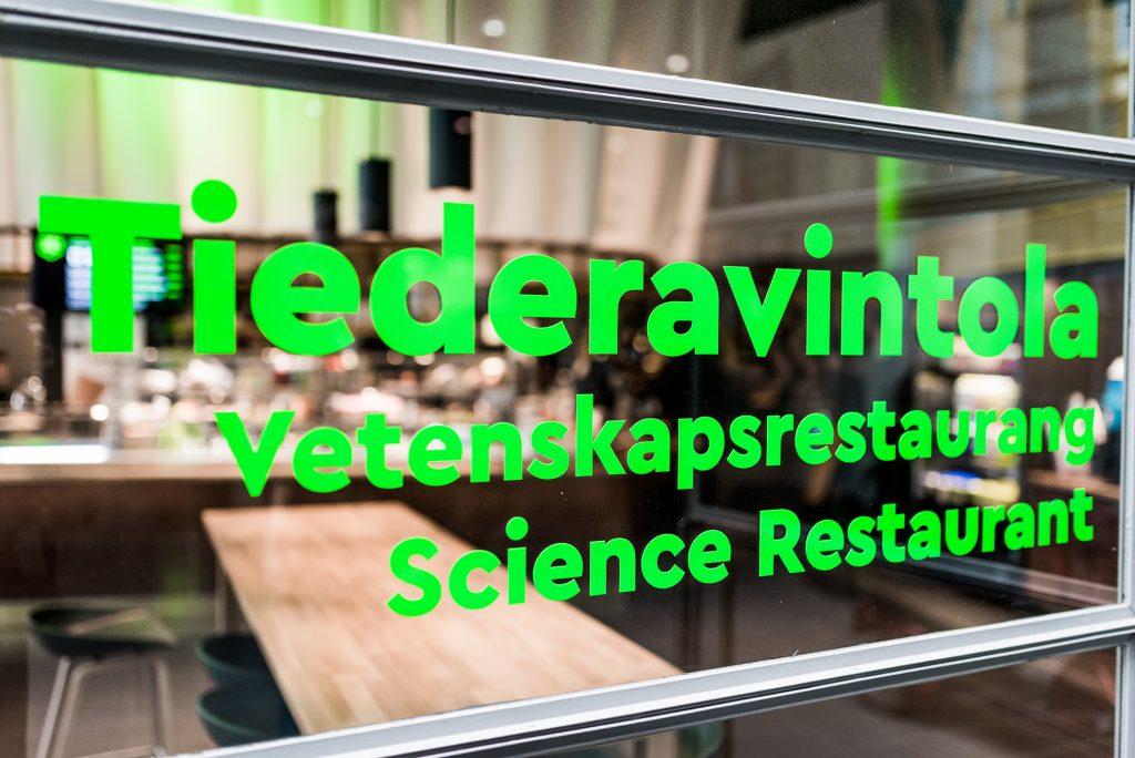 Tiederavintolan nimi kolmella kielellä TIederavintolan ovessa.