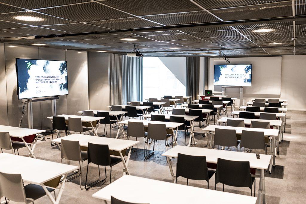 Kuvassa Heurekan ryhmätyötila, jossa kaksi digitaalista näyttöä sekä paljon pöytiä ja tuoleja.