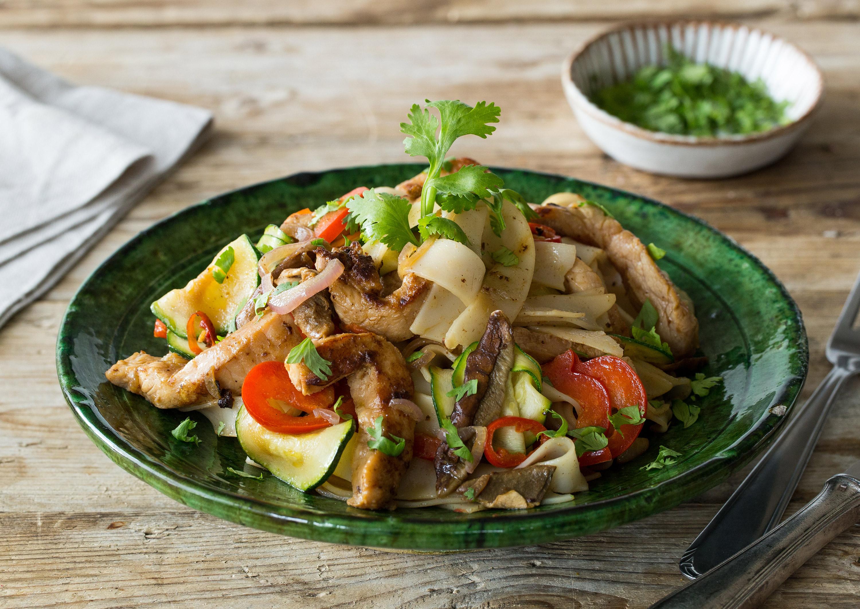 Thai-Street Food: Reisnudelpfanne mit Erdnussbutter, mariniertem Schweinefleisch und buntem Gemüse