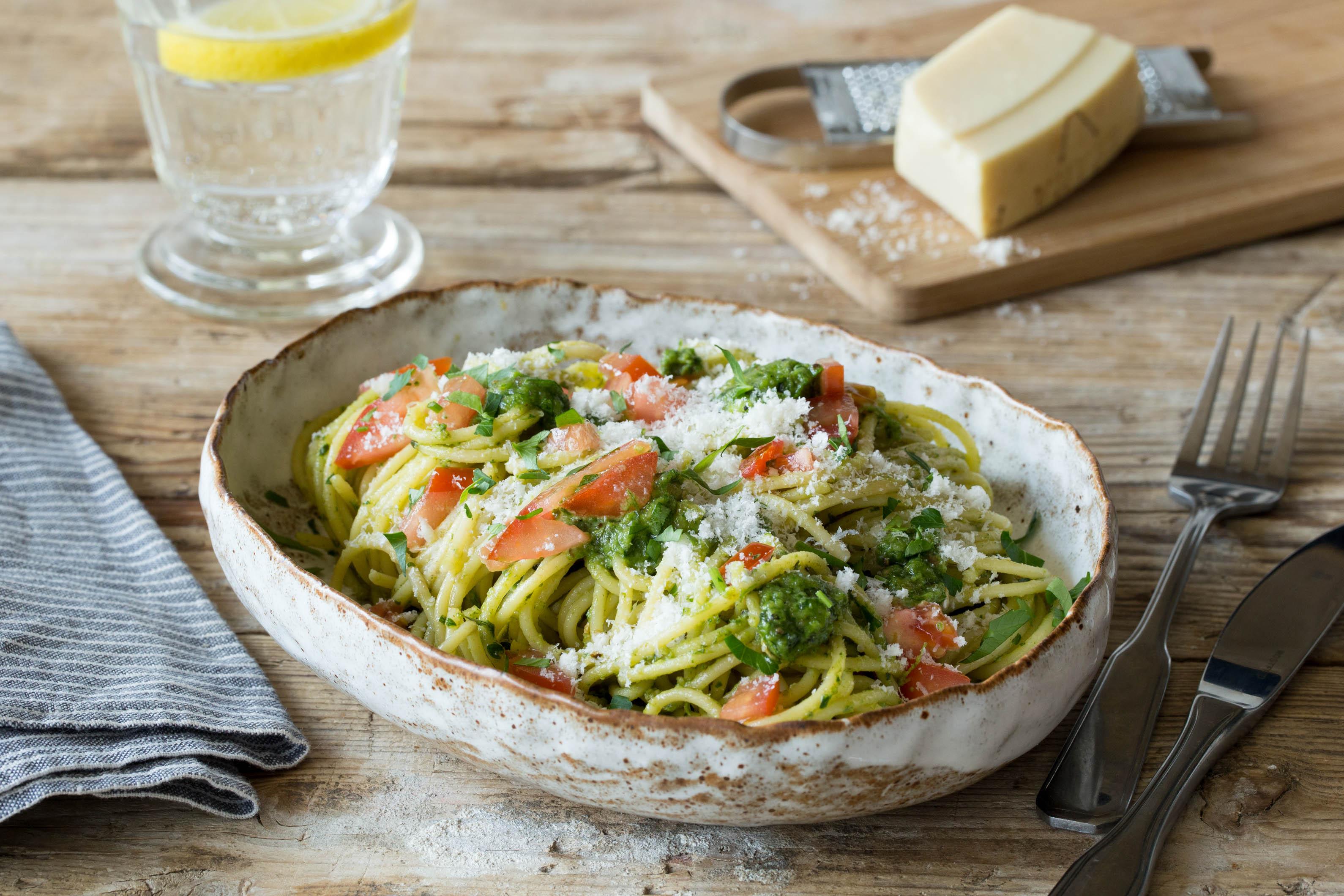 Herzhafte Sauerampfer-Pesto-Spaghetti mit Tomatenwürfeln und frischem Parmesan
