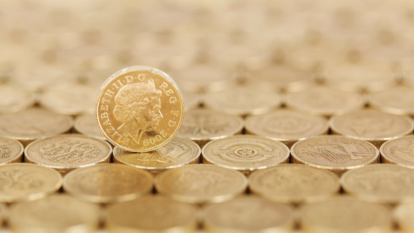Pound coin rolling over other coins