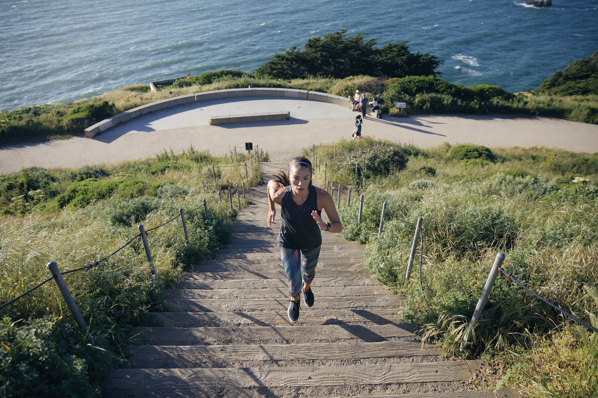 woman wearing fitbit ionic running up stairs next to an ocean view