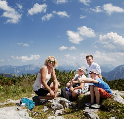 Happy family with two boys on the top of a mountain after a long hike up in Alps, Austria