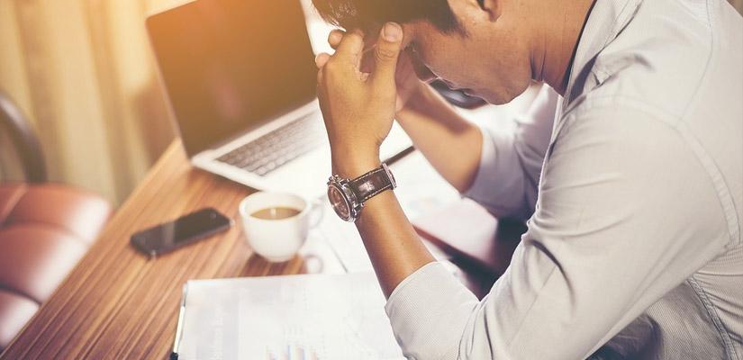 stressed man reading bills