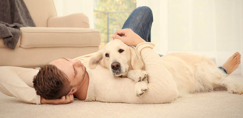 man lying on warm floor with dog