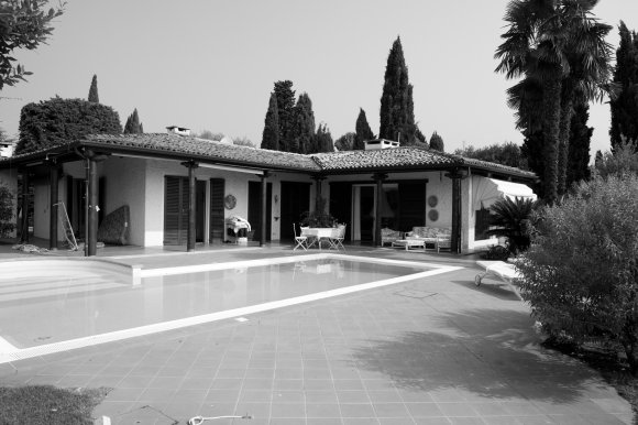This renovation is going to change the identity of the existing house. The extension of the interior space has suggested the demolition of the sloping roof and construction of a large terrace from where relaxing and looking at the Lago di Garda. The extension is clearly marked with a white painted plaster, while the old part of the house is clad with local stone.