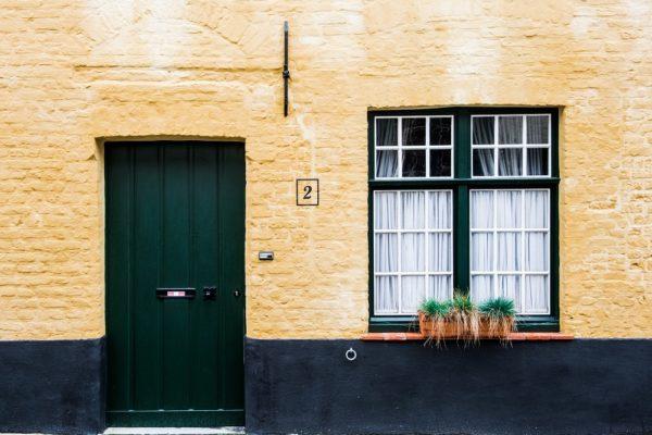 puerta de entrada verde en pared amarilla
