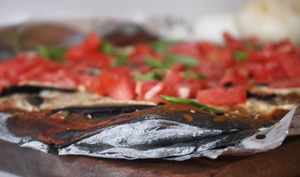 Pizza nera à l'encre de seiche: champignons, tomates fraîches et basilic