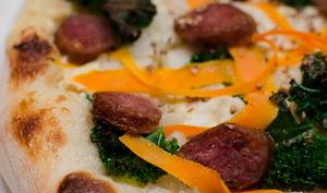 Pizza au chou kale, aux tagliatelles de carottes et aux saucisses fumées