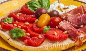 Pizza à la garniture crue de jambon, tomates et burrata