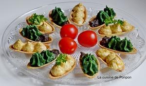 Amuse bouche garni de caviar de pois chiches au chèvre, de pesto aux épinards et confit à la truffe d'été