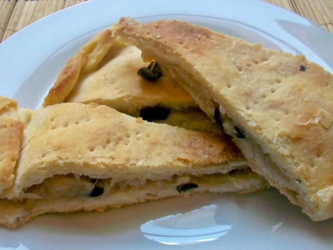 La focaccia fourrée aux oignons, câpres et olives noires