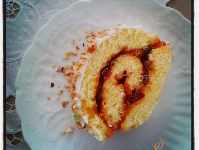 Gateau roulé à la confiture d'abricots et fruits confits , glaçage vanille et noisettes torréfiées hachées