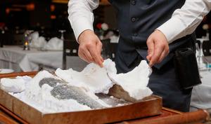 Service d'un poisson cuit en croûte de sel.
