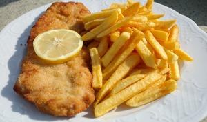 Filet de poisson pané sur assiette blanche avec frites