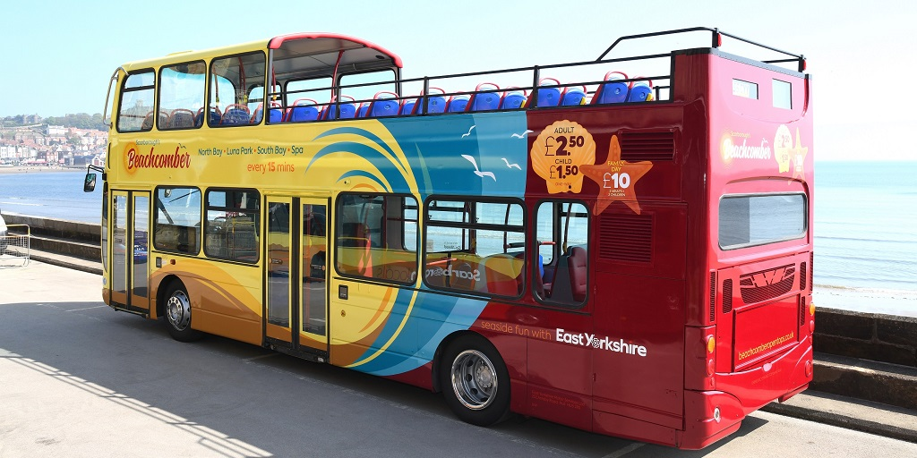 A colourful open top bus with Scarborough's South Bay in the background