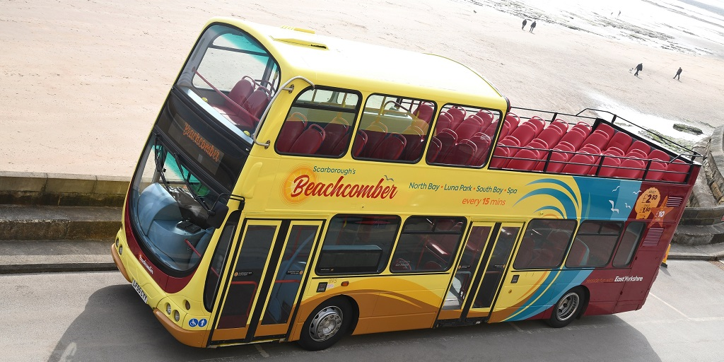 A Beachcomber open top bus besides the beach