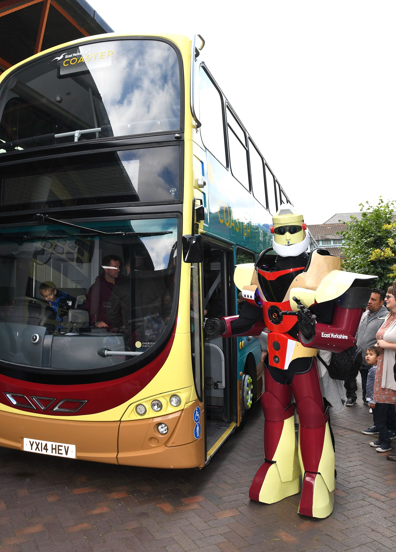 A large colourful robot stands by a bus