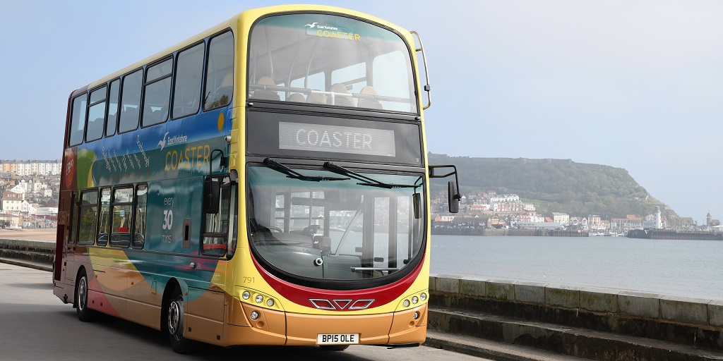 A colourful Coaster bus with Scarborough's South Bay in the background