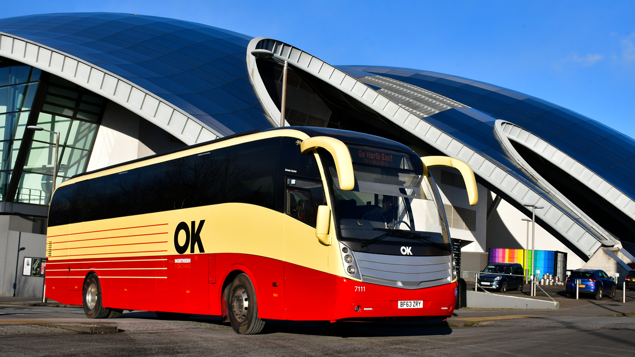 OK branded Northern Coaching coach from Go North East in front of Sage Gateshead